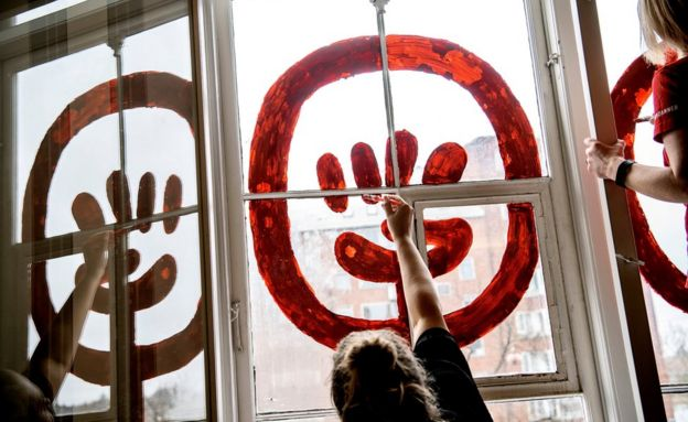 Mujer pintando una ventana en el Día de la Mujer en Dinamarca