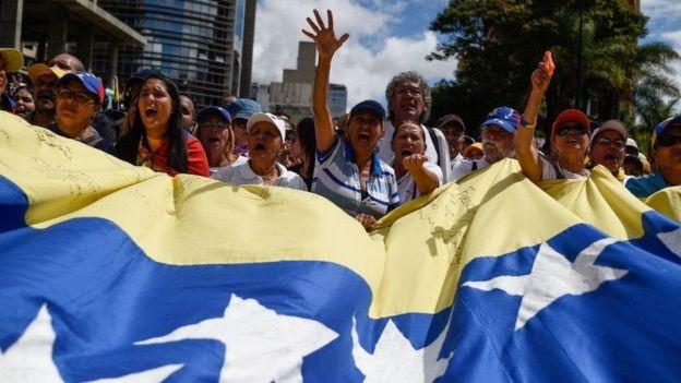 Dezenas de venezuelanos gritam e seguram bandeira do país em protesto na rua