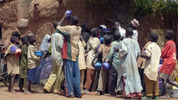 A crowd of child beggars struggle for alms from a man in northern Nigeria's Kano city (file photo)