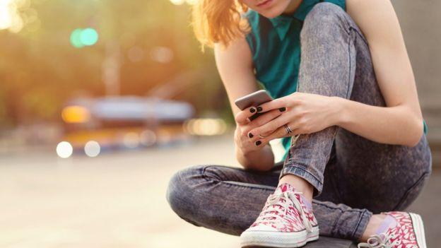 Jóven con su celular