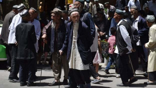 Uighur men are seen leaving a mosque after prayers in Hotan in China's Xinjiang region