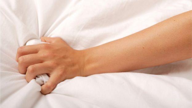 Mulher segura lençol da cama