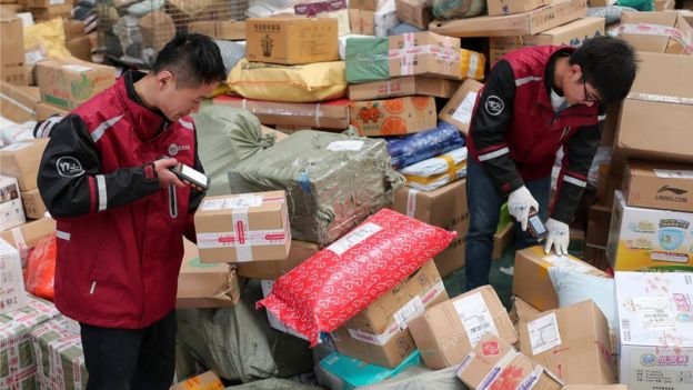 Workers scanning parcels in distribution centre