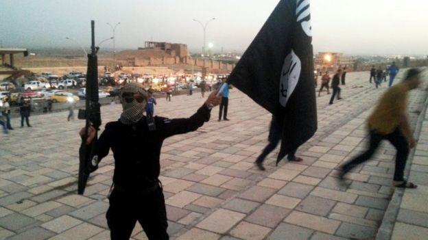 İslami bir Irak Devleti ve İskoç Levant (ISIL) militanı, 23 Haziran 2014'te Musul kentindeki bir sokakta siyah bir afiş ve bir tüfek tutuyor