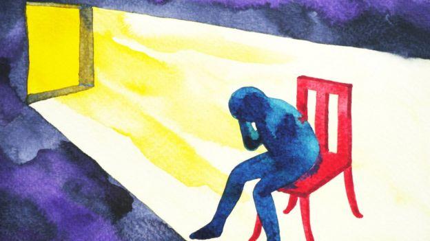 Ilustração mostra boneco dentro de casa sentado, cabisbaixo, protegendo com a mão a cabeça da luz que chega da janela