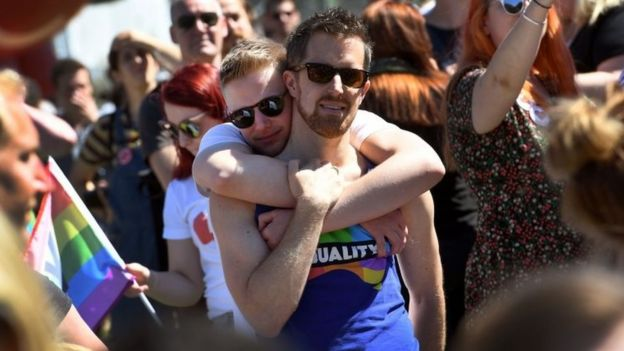 Two men embrace at a celebration in Sydney