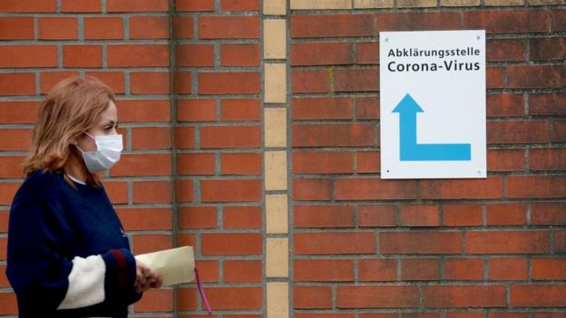 A woman, wearing a face mask, walks past a sign guiding people to the entrance of a corona testing station at the Vivantes Wenckebach hospital in Berlin