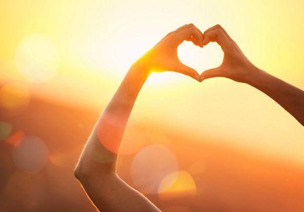 Una persona dibujando un corazón al unir sus manos.
