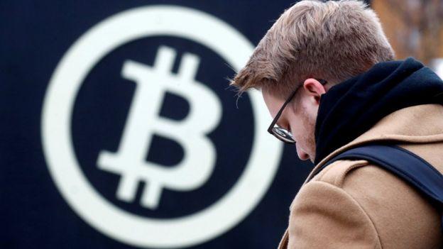 Um homem em frente ao logo da Bitcoin