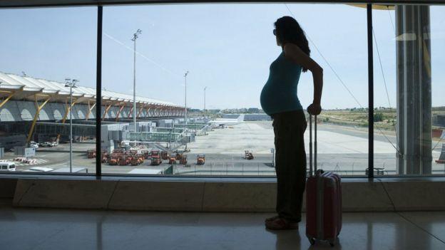 Беременная женщина с чемоданом