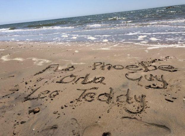 Nombres escritos en la arena de la playa.