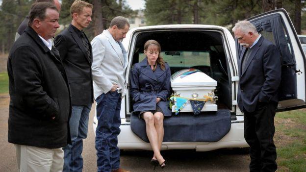 mulher sentada em carro fúnebre ao lado de caixão