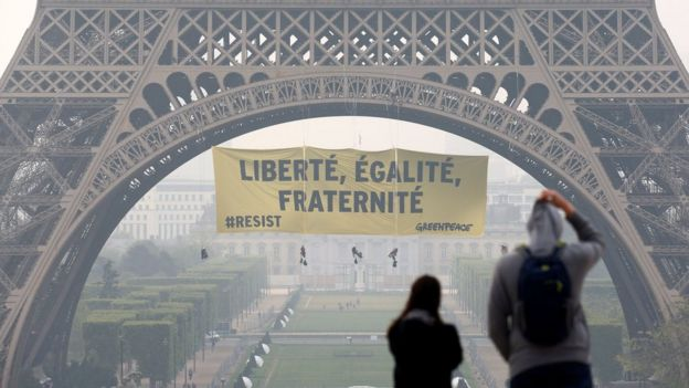 Tourists walk at Trocadero square as activists from the environmentalist group Greenpeace unfurl a giant banner on the Eiffel Tower which reads