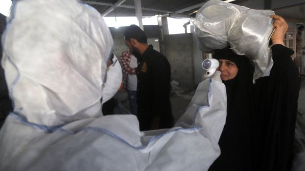 A health worker checks the temperature of an Iraqi woman upon her arrival at the Shalamcheh border crossing with Iran (20 February 2020)