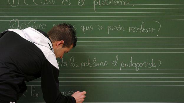 Hombre escribe en español en una pizarra.