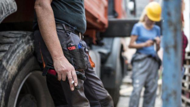 Trabalhador munido de equipamentos manuais, como estilete, segura cigarro em ambiente com grandes veículos e outros trabalhadores com capacete