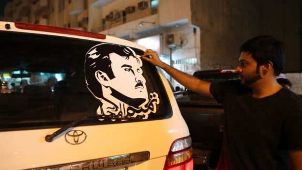 Doha man puts on a car a sticker portraying Qatar's Emir Sheikh Tamim bin Hamad Al-Thani