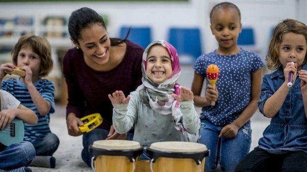 Una mujer con unos niños de distintos tonos de piel.