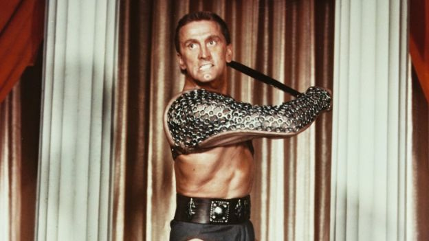 Kirk Douglas, dressed in a chainmail armguard and loincloth, brandishes a weapon with a snarl in this film still