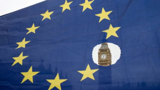 a pro-remain protester holds up an EU flag with one of the stars symbolically cut out in front of the Houses of Parliament,