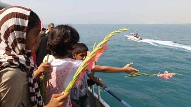 Personas arrojan flores el mar