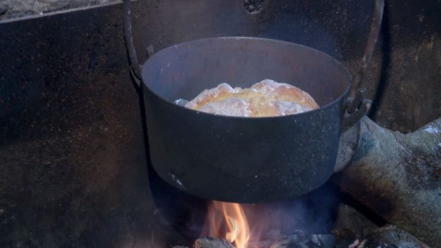 A pot of soda bread cooking over an open fire