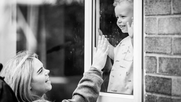 Charlotte Cole touches window to greet son