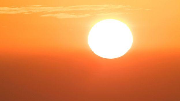 Um sol poderoso sobre um céu intensamente laranja.