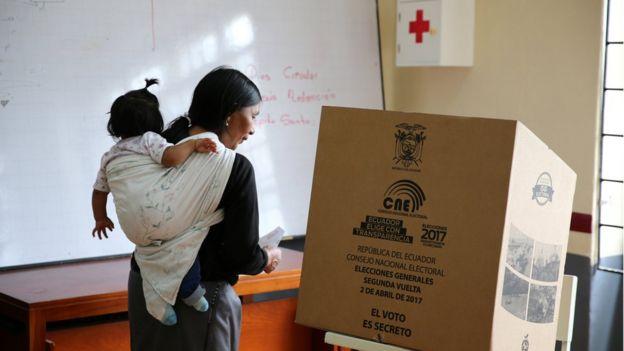 Una mujer con un niño cargado acude a votar en un centro electoral en Ecuador.