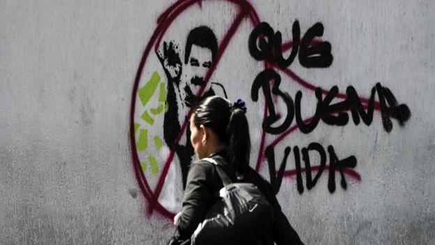 Mulher passa em frente a grafite que retrata Nicolás Maduro