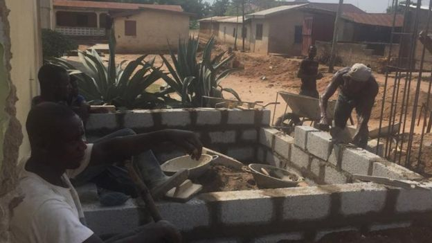 Construct workers building a wall in Ghana