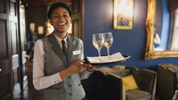 A smiling waitress in a waistcoat holds a tray with two glasses of white wine on