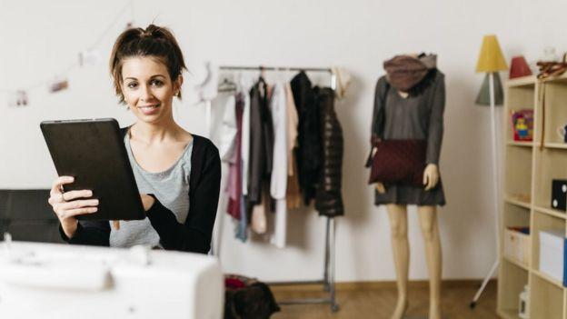 Mujer en Estonia con tableta en negocio textil.