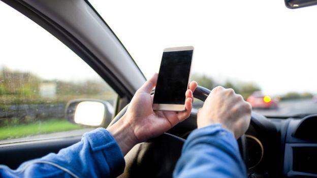 Una persona al volante con un celular