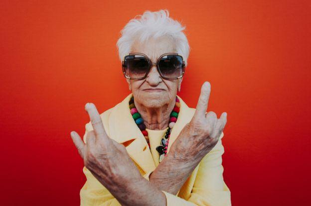 Una mujer mayor con pose rockera