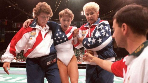 US gymnast Kerri Strug (2nd L) screams in pain as she is carried from the floor by team officials after she injured her ankle at 1996 Olympics