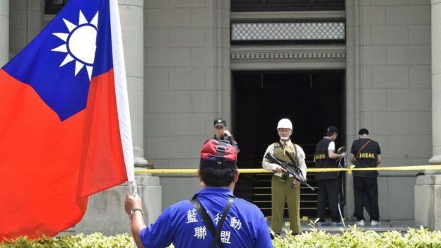 Un manifestante con una bandera de Taiwán frente a un edificio oficial en Taipei.