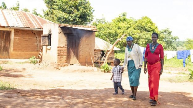 A traditional birth attendant walks with a pregnant mother