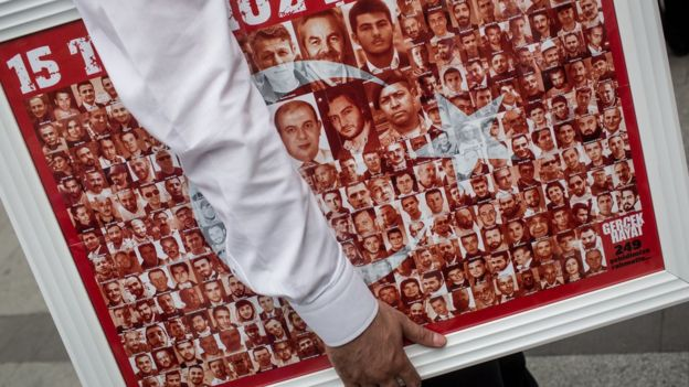 Türk bayrağını oluşturan fotoğraflar, birisinin kolunun altındaki posterde