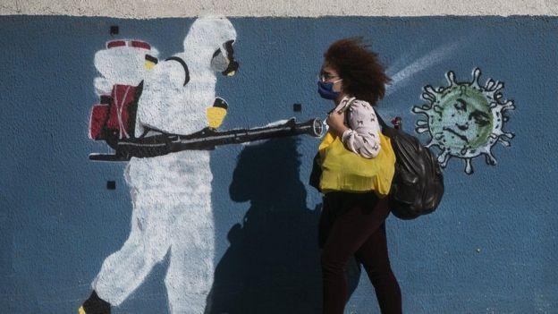 Una mujer con mascarilla caminando al lado de un grafiti de un trabajador de salud pública.