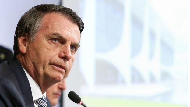 Bolsonaro fala no microfone em posição de perfil, com imagem da fachada do Palácio do Planalto ao fundo