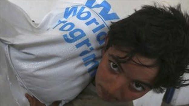 A boy receives humanitarian aid in Duma, Damascus March 29, 2014