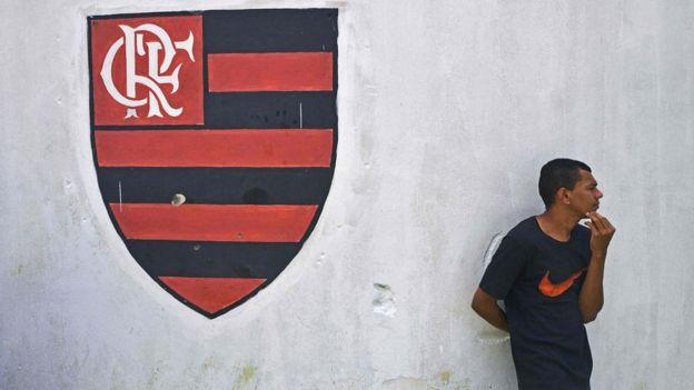 Homem ao lado de escudo do Flamengo pintado; incêndio em centro de treinamento deixou dez mortos