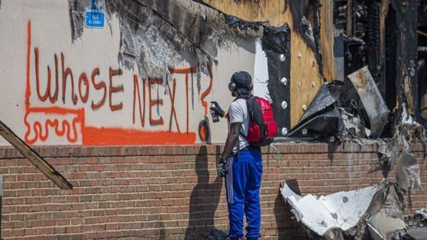 A man spray paints a message onto the wall of a restaurant destroyed after the Atlanta police shooting on 12 June