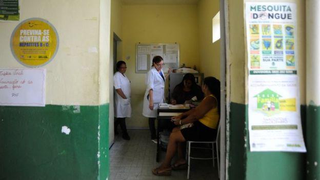 Profissionais de saúde e paciente dentro de clínica de saúde da família na Baixada Fluminense, RJ