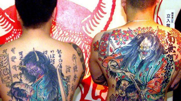 Dos hombres con tatuajes en sus espaldas