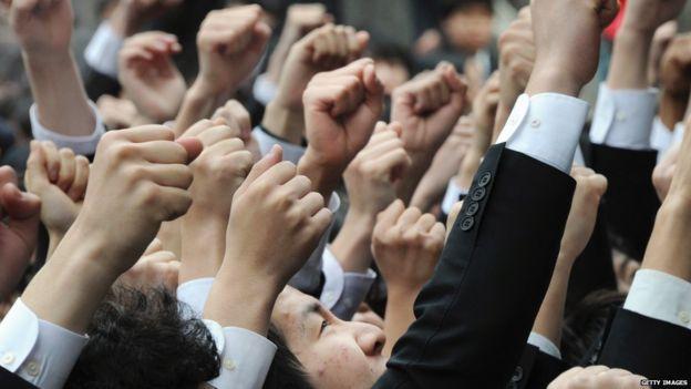 Alunos japoneses com mãos erguidas