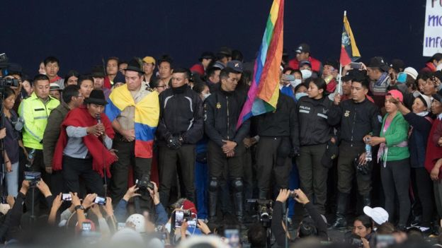 Captive police officers are paraded in front of a crowd of thousands in Quito