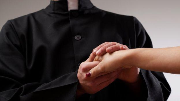 Sacerdote sosteniendo la mano de una mujer
