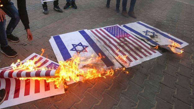 متظاهرون يحرقون العلمين الأمريكي والإسرائيلي